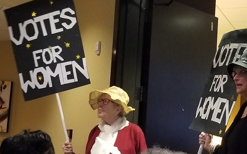 Votes for Women signs held by AAUW NC members in costume.