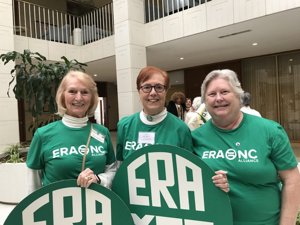 "Three AAUW members in green ERA Tshirts with green ""ERA YES"" rounds."